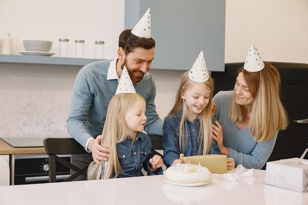 Rodzina i dwie córki świętują urodziny w kuchni. ludzie noszą imprezowe kapelusze. dziewczyna trzyma pudełka z prezentami.