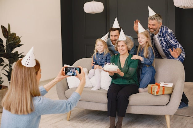 Rodzina i dwie córki świętują urodzinydwóch mężczyzn i dwie dziewczynki siedzą na kanapie mama robi im zdjęcie