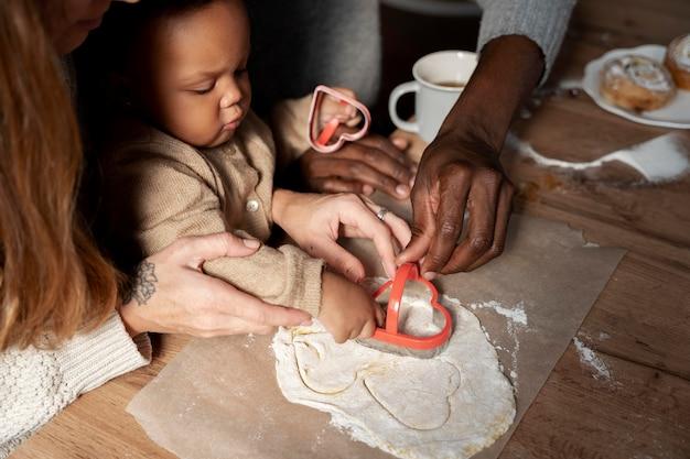 Rodzina i dziecko robią ciasteczka z bliska