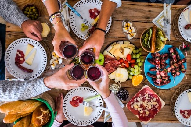 Rodzina i przyjaciele brzękają i mają faun w domu podczas świątecznej kolacji