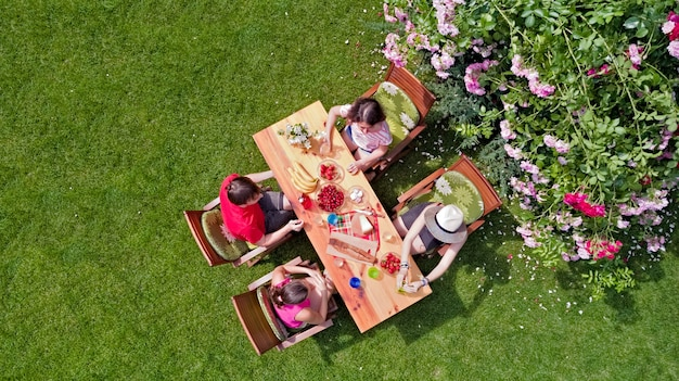 Rodzina i przyjaciele jedzą razem na świeżym powietrzu na letnim przyjęciu w ogrodzie. widok na stół z jedzeniem i napojami z góry. koncepcja wypoczynku, wakacji i pikniku