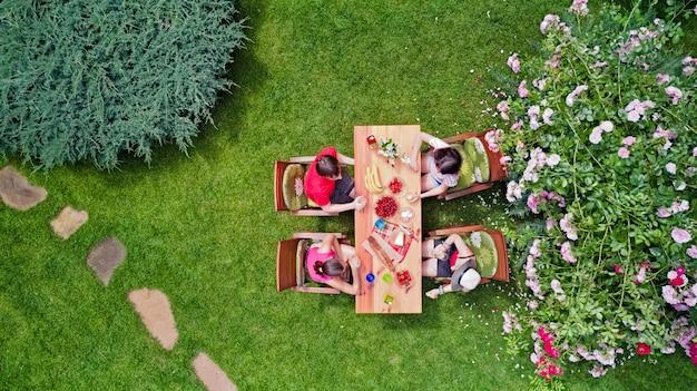 Rodzina i przyjaciele jedzą razem na świeżym powietrzu na letnim przyjęciu w ogrodzie