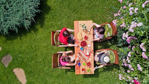 Rodzina i przyjaciele razem jeść na świeżym powietrzu na przyjęcie w ogrodzie letnim. widok z lotu ptaka stół z jedzeniem i napojami od above. koncepcja wypoczynku, wakacji i pikników