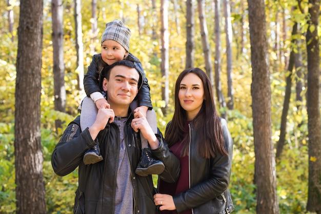 Rodzina, jesień, koncepcja ludzi - młoda rodzina spaceru w parku jesienią. córka siedząca na tacie