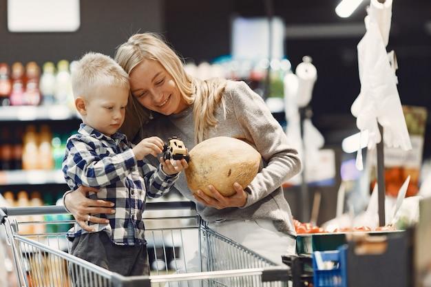 Rodzina kupuje artykuły spożywcze. matka w szarym swetrze.