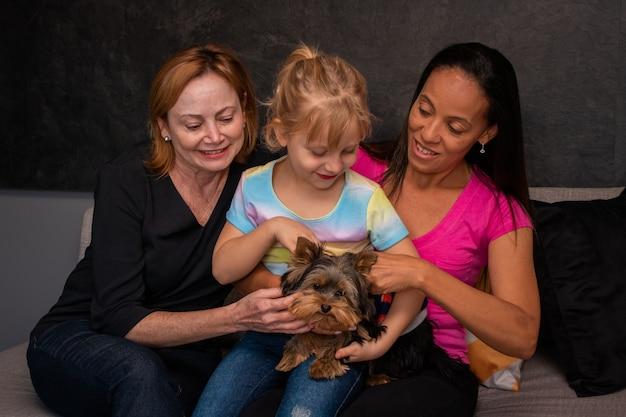 Rodzina lesbijek i ich córka siedzą na kanapie ze swoim psem