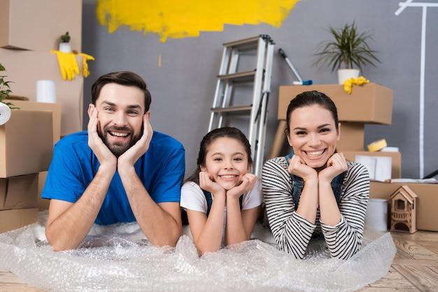 Rodzina leżąca na folii bąbelkowej planuje zrobić naprawy w domu