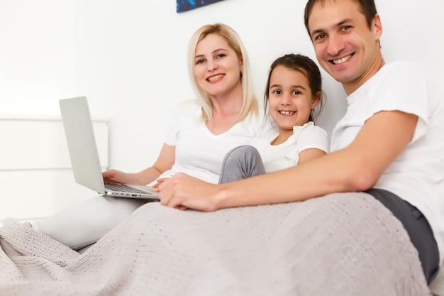 Rodzina leżąca w łóżku z laptopem