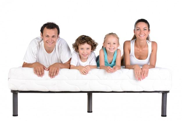 Rodzina leży na materacach, na białym tle