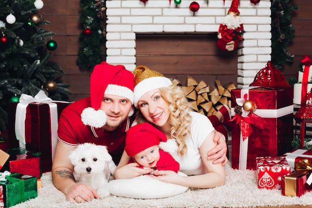 Rodzina leży na podłodze przy kominku z małym synem i psem i uśmiecha się do kamery