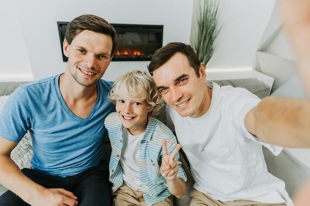 Rodzina lgbt, para gejów z adoptowanym synem - homoseksualni rodzice z dzieckiem bawią się w domu