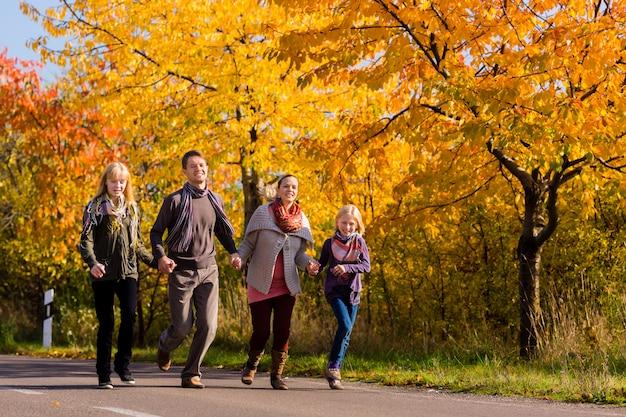 Rodzina ma spacer przed kolorowymi drzewami w jesieni