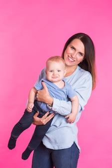 Rodzina, macierzyństwo, rodzicielstwo, ludzie i koncepcja opieki nad dzieckiem - szczęśliwa matka trzyma urocze dziecko nad różową ścianą.