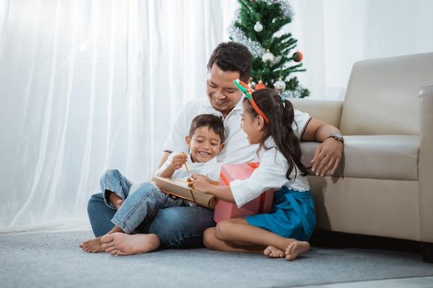 Rodzina malajska wspólnie otwierająca prezenty świąteczne w domu