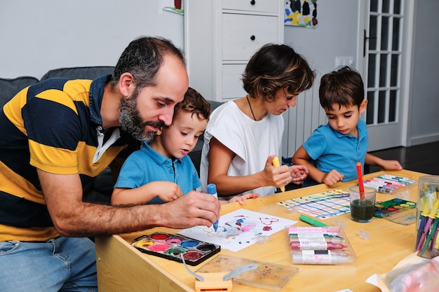 Rodzina malująca i bawiąca się z dziećmi