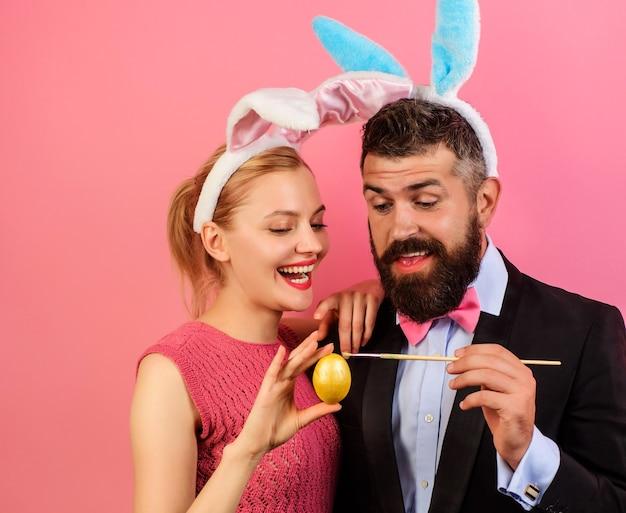 Rodzina malująca jajka na wielkanoc. para w uszach królika z pisanką.