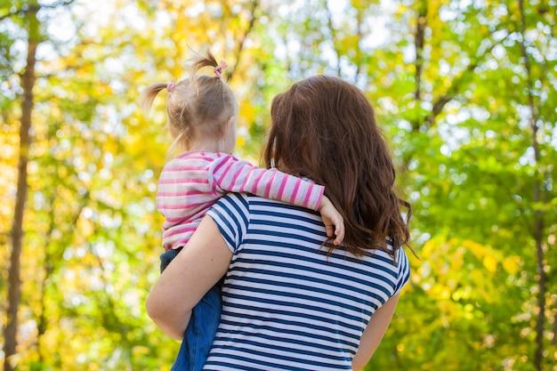Rodzina mama i córka na spacerze w parku jesienią. w bezpiecznych rękach mamy