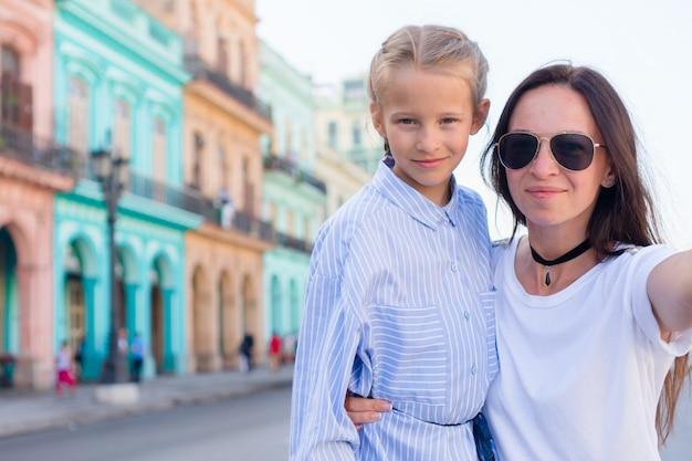 Rodzina mama i mała dziewczynka bierze selfie w popularnym terenie w starej hawanie, kuba. małe dziecko i młody mofther na zewnątrz na ulicy w hawanie