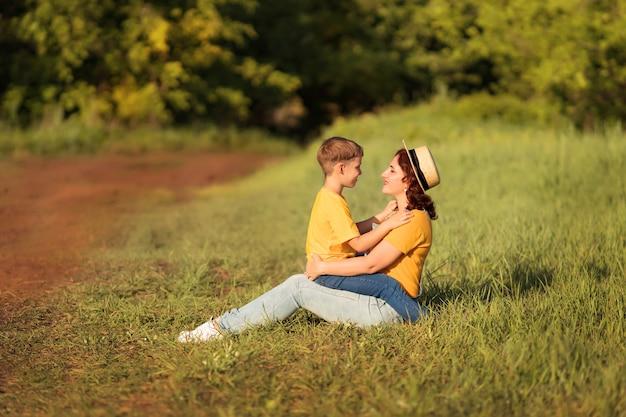 Rodzina: mama i synek przytulają się i całują o zachodzie słońca latem