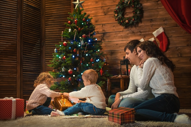 Rodzina mama, tata, córka syna świętują boże narodzenie w udekorowanym domu z choinką