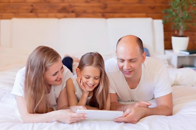 Rodzina, mama, tata, córka w łóżku są zaangażowani w tablet.
