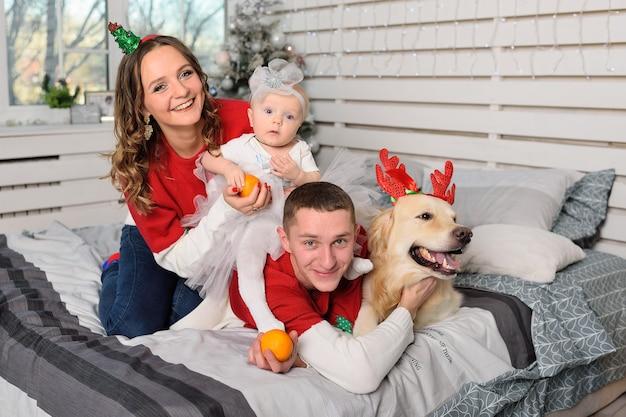 Rodzina-mama, tata i córeczka w bożonarodzeniowych swetrach