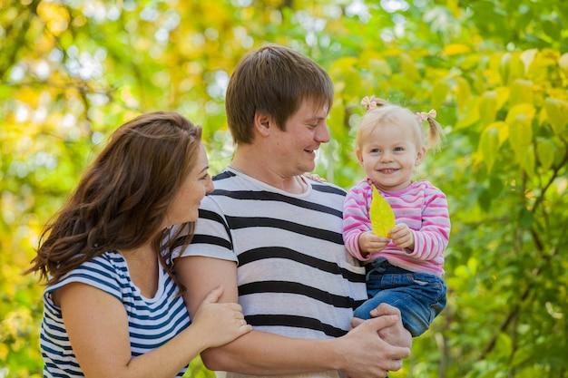 Rodzina mama, tata i córka na spacer po parku jesienią. dziecko jest w bezpiecznych rękach ojca