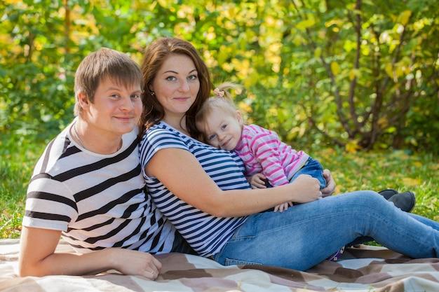 Rodzina mama, tata i córka na spacer po parku jesienią. piknik liściasty
