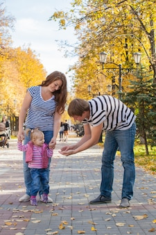 Rodzina mama, tata i córka na spacer po parku jesienią.