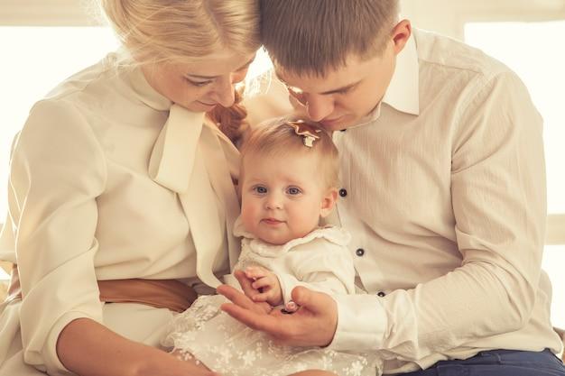 Rodzina, mama, tata i córka obejmują razem piękne i szczęśliwe zbliżenie