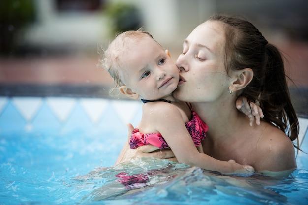 Rodzina matka i córka córeczki pływają w odkrytym basenie piękne i szczęśliwe