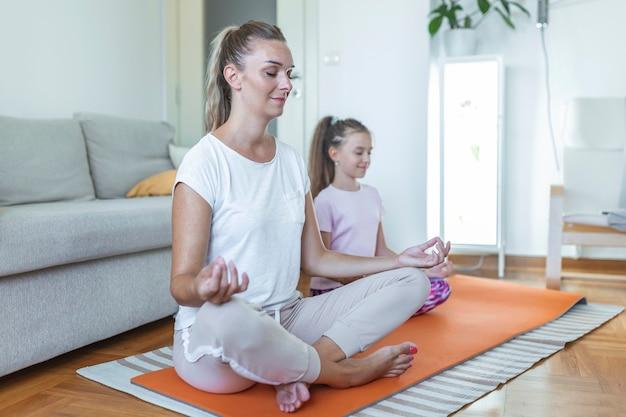 Rodzina matka i córka dziecka zajmują się fitnessem, jogą, ćwiczeniami w domu. mama i córka ćwiczą jogę