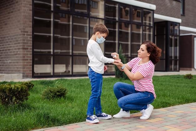 Rodzina matka i syn na ulicy. dziecko nosi ochronną maskę medyczną podczas epidemicznego wirusa wieńcowego lub grypy. sprzęt ochrony osobistej. matka daje swojemu dziecku środek antyseptyczny
