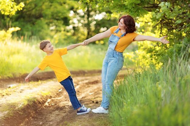 Rodzina: matka i syn spacerują, trzymają się za ręce, bawią się latem