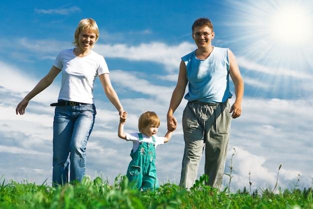 Rodzina matka ojciec i dziecko pod błękitnym niebem