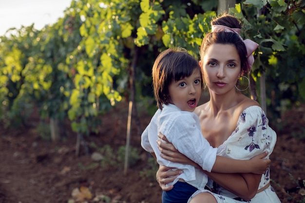 Rodzina matka w sukience z synem spacerującym po winnicy w lecie we włoszech