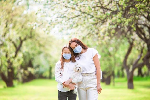 Rodzina matki i córki w kwitnącym ogrodzie wiśniowym w maskach ze szczeniakiem
