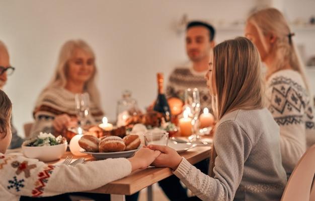 Rodzina modląca się przy świątecznym stole