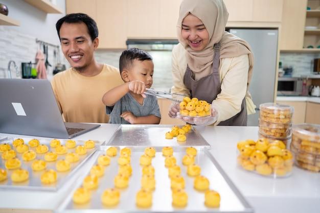 Rodzina muzułmańska gotuje razem w domu tartę z nastarem, używając laptopa