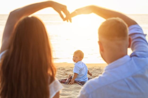 Rodzina na plaży koncepcji, kaukaski chłopiec lokalizacji i gospodarstwa piasku na tropikalnej plaży w czasie zachodu słońca