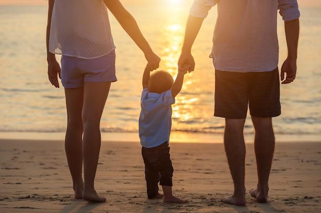 Rodzina na plaży, matka trzyma rękę syna i spacery, grając na plaży z mężem