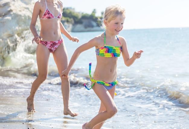 Rodzina na plaży o zachodzie słońca. matka i córka biegają razem.