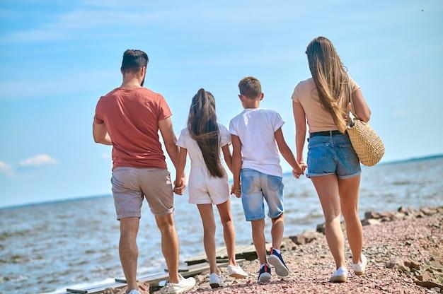 Rodzina na plaży. rodzina spacerująca po brzegu trzymająca się za ręce