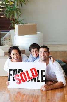 Rodzina na podłodze po zakupie domu z copyspace