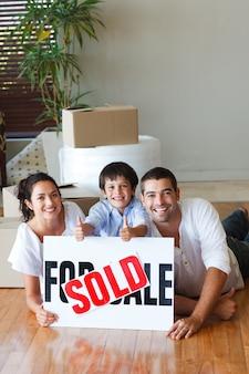 Rodzina na podłodze z pudełka po zakupie domu