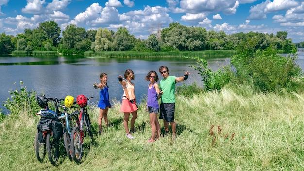 Rodzina na rowerach na rowerze na świeżym powietrzu, aktywni rodzice i dzieci na rowerach, widok z góry szczęśliwej rodziny z dziećmi relaksującymi się w pobliżu pięknej rzeki z góry, sport i fitness