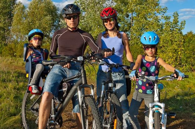 Rodzina na rowerze na świeżym powietrzu. szczęśliwi rodzice z dwójką dzieci na rowerach