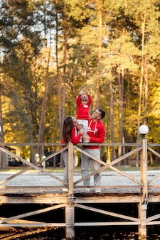 Rodzina na spacerze w jesiennym parku nad stawem. ojciec i mama trzymający córkę za ręce.