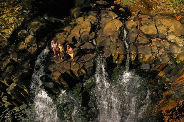 Rodzina na tle wodospadu rochester na wyspie mauritius z wysokości. wodospad w dżungli tropikalnej wyspy mauritius