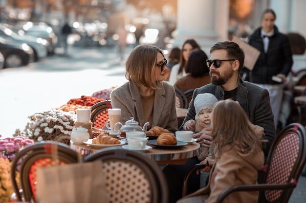 Rodzina na wycieczce na plac europejski w ulicznej kawiarni zatrzymała się na przekąskę.